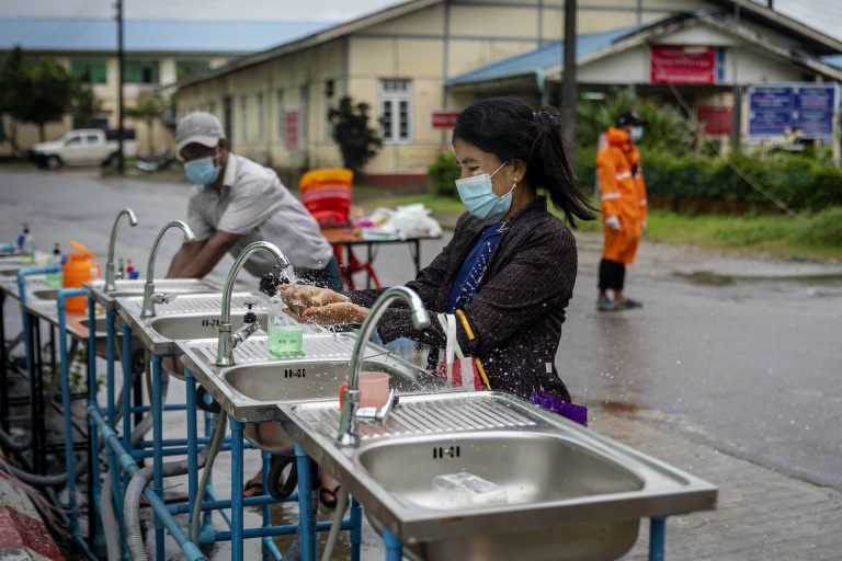 A woman washes her hands at the entrance to Sittwe General Hospital in Rakhine State on August 24. (Hkun Lat | Frontier)