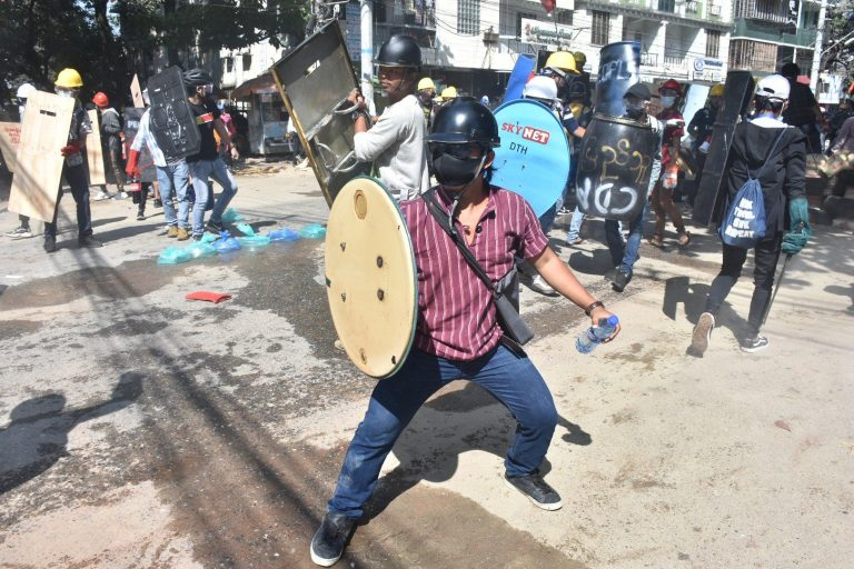 A protester in Yangon's Sanchaung Township holds up a makeshift shield to protect from police batons and rubber bullets on March 4. (Frontier)